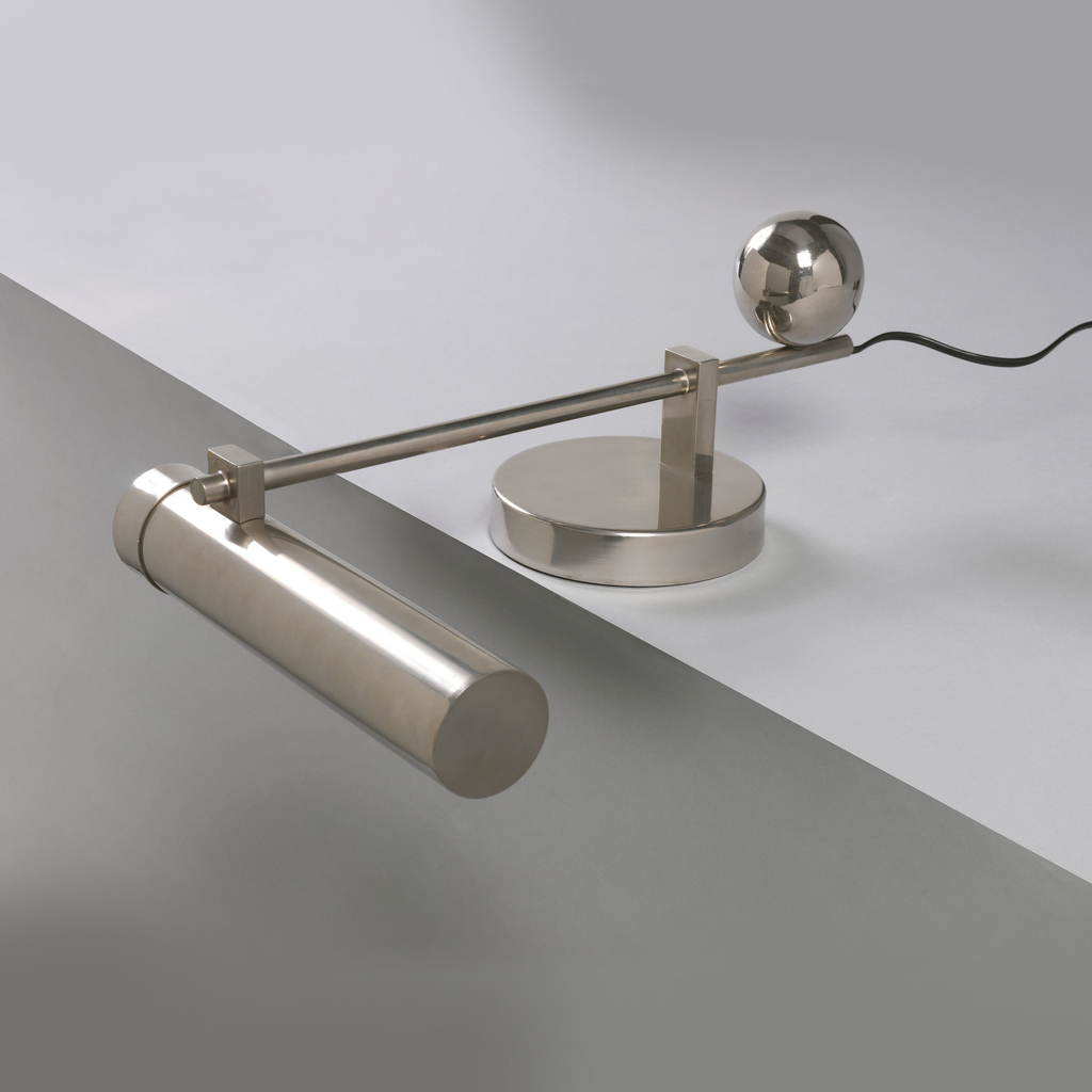 Lamp composed of geometric elements: horizontally mounted cylindrical bulb cover on rod as adjustable arm with chromed metal ball counterweights at back; low circular base; bakelite electrical fittings.