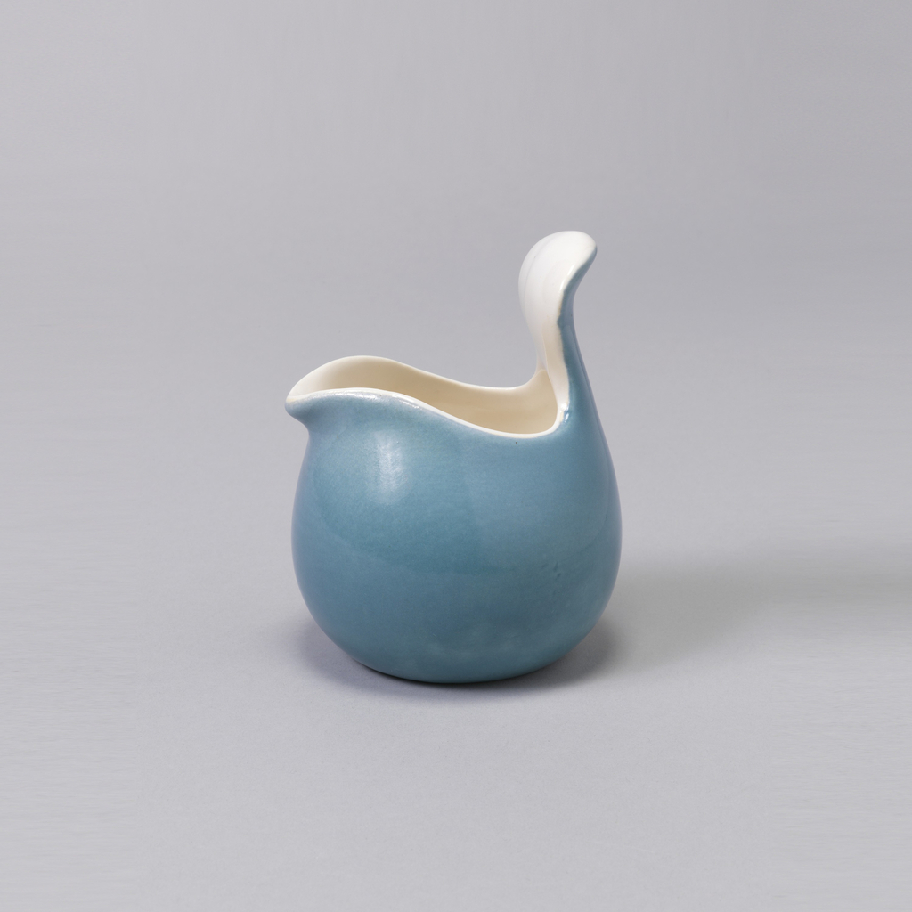 Bulbous body rising to wide mouth shaped to form spout and raised outturned tab handle; glazed blue on exterior, off-white on interior.