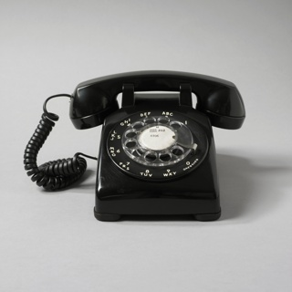 """Black rectangular plastic body with sloping top; circular clear plastic dial in center, surrounded by white numbers 1 to 0, the letters A to Y, and the word """"OPERATOR"""", all arranged in a circle around the dial, their positions corresponding to fingerholes in dial. Barbell-shaped handset of black plastic sits in cradle on top of body; coiled black wire at one end of handset plugs into telephone body."""