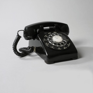 "Black rectangular plastic body with sloping top; circular clear plastic dial in center, surrounded by white numbers 1 to 0, the letters A to Y, and the word ""OPERATOR"", all arranged in a circle around the dial, their positions corresponding to fingerholes in dial. Barbell-shaped handset of black plastic sits in cradle on top of body; coiled black wire at one end of handset plugs into telephone body."