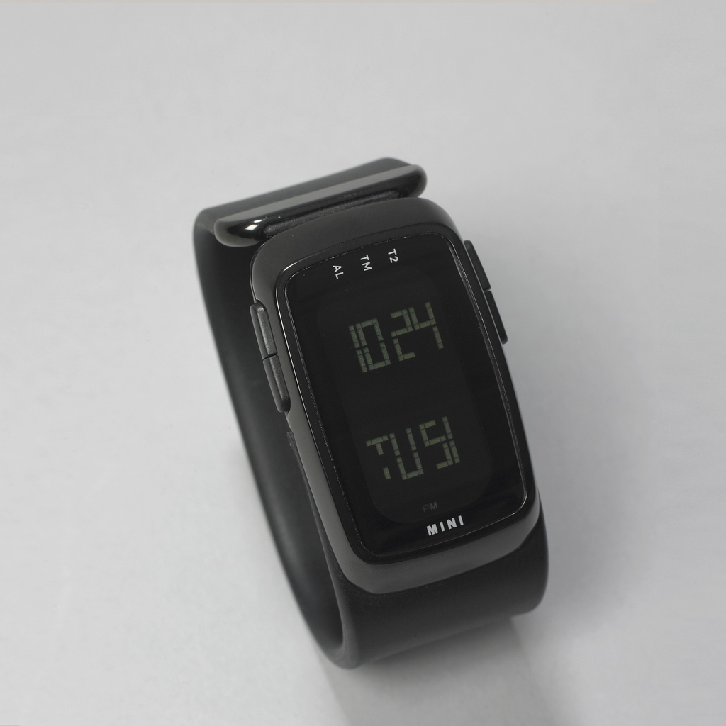 Rectangular digital watch with bevel-edged black-enameled stainless steel bezel on wide, flat, black rubber strap terminating in black-enamelled stainless steel band ; four flat, rectangular fuction buttons on bezel; the word MINI on one side of read out, T2, TM, AL, on the other. Digital read out can be changed from horizontal to vertical orientation.