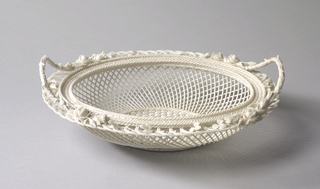 Oval form, with pierced latticework body, the rim and cover encrusted with flowers, clovers, and thistles, with branch-form handles at the ends.