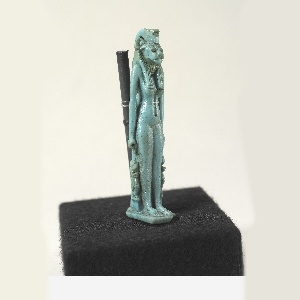 Standing in frontal position on flat base, with vertical support at back. Lion's head with pierced crest. Two cynocephali, representing the god Thoth, attached to legs in crouching position. Figure represents the goddess Sakhmet.