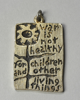 "Upright rectangular pendant with engraved decoration consisting of the slogan, ""war is not healthy / for children and other / living things,"" interspersed between the leaves and stem of a stylized petaled flower. Small ring at top of pendant."