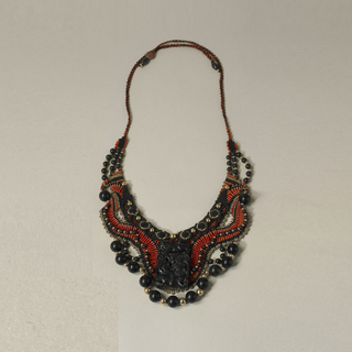 Small, flat collar woven and beaded, predominantly black and red; gold and black jade beads; central carved black jade pendant lays on top.