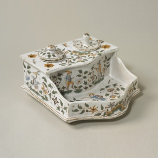 Shaped inkstand (a) with separate inkpot (b) with lid (c), and sander (d); green and ochre decoration of flowers, foliage, and figure. Sampson in the style of 18th-century Moustiers.