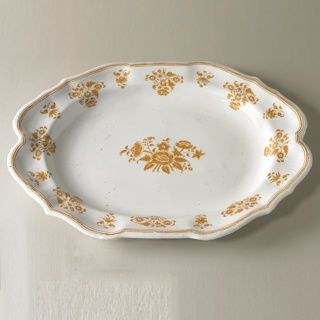 Oval tureen (a) with stepped domed lid (b) having shaped edge and center knop; oval stand (c) with shaped edge; all with white ground decorated with ochre flowers and foliage; narrow band along edges of cover and stand.