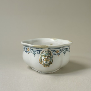 Lobed oval form with mascaron and blue and ochre decoration at rim.