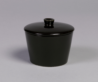 Body (a) flat based, straight sides flared outward toward plain lip. Slightly domed cover (b) with circular finial. Both overall black gloss glaze. Underside of body (a) with unglazed foot ring; (b) with unglazed flange underside.