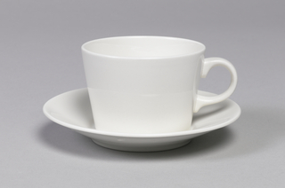 White tappering cylindrical cup (a) with D-shaped handle; white circular saucer (b) with wide, angled rim.