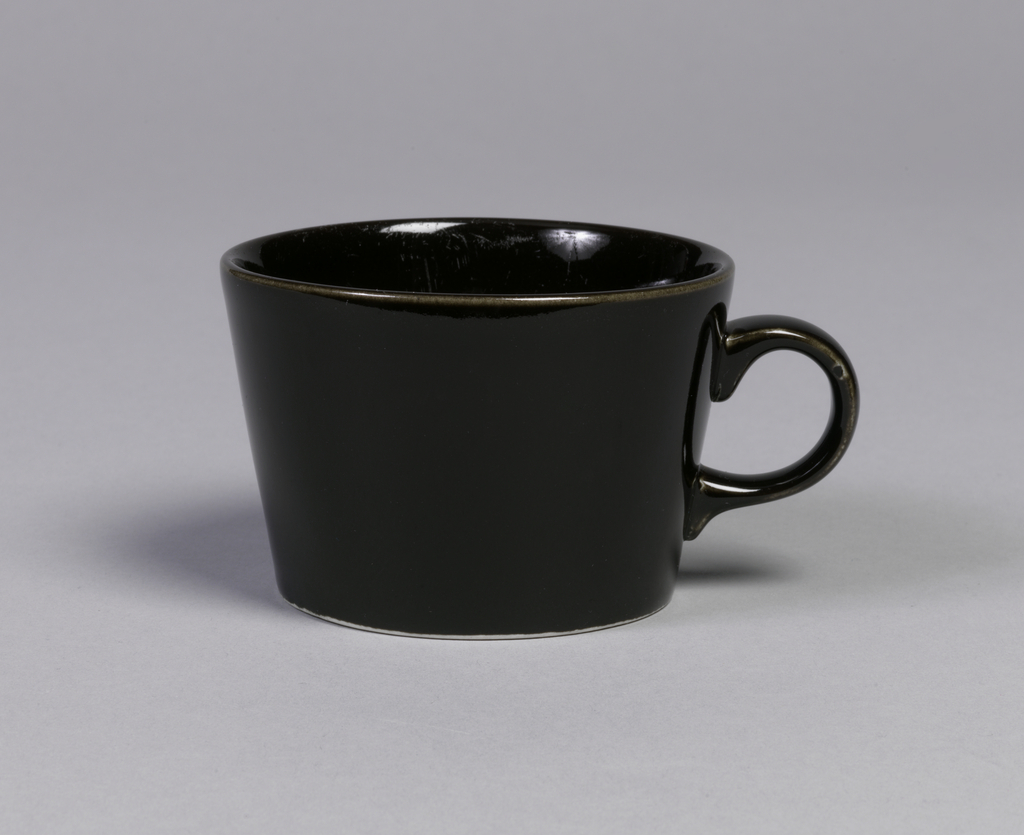 "Cup with straight sides flared to plain lip.  Applied ""C"" shaped handle."