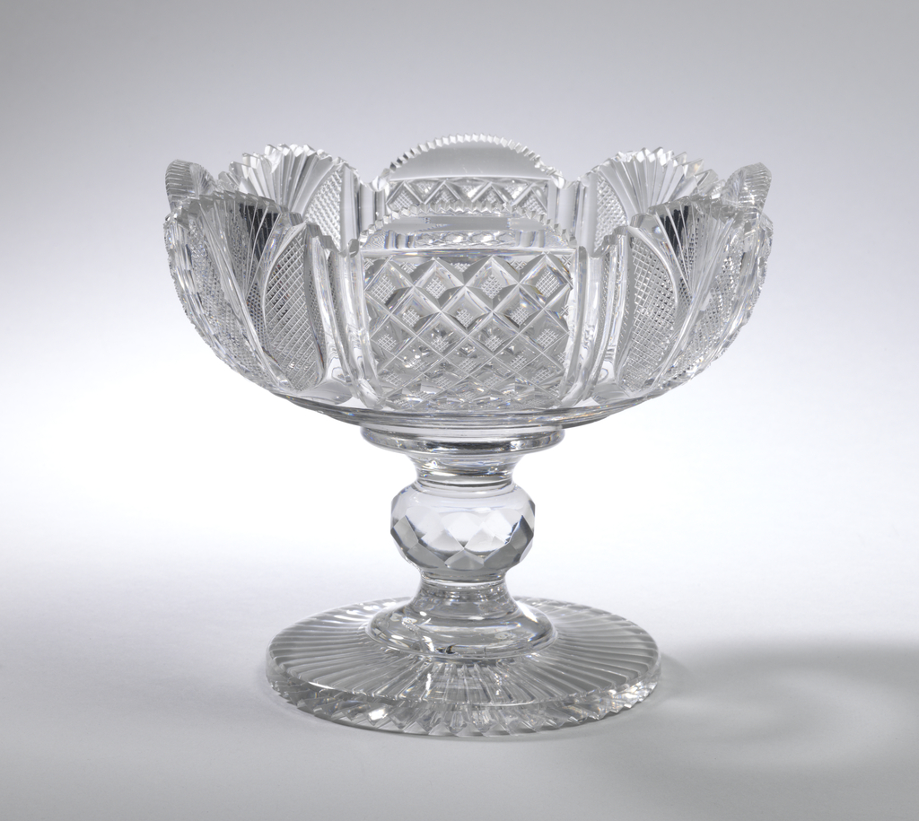 Shallow round bowl cut with alternate panels of strawberry diamonds and panels with fan cutting and tiny diamonds, top edge scalloped; tall stem with round faceted knop, flat circular base with radial cutting on bottom; glass has greyish case, heavy.