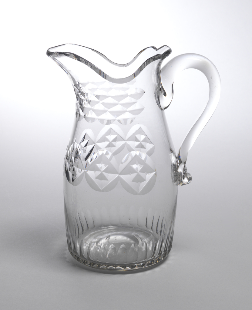 Barrel-shaped body tapering at neck, shaped lip with pouring spout, loop handle; cut around center with band of large printies enclosing faceted diamonds, around neck with hollow faceting, around base with short vertical fluting; ground pontil mark bottom.