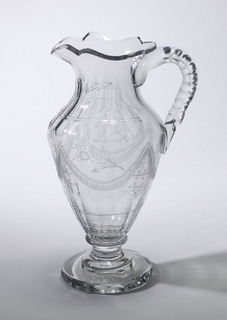 "Urn-shaped body, tapered neck, shaped lip with pouring spout, loop handle with 2 rows of cut facets along sides; sides decorated with engraved decoration of swags, flowers and the initials ""S A N"" under spout, fluting above and below; tapered foot on spool stem and flat disk-shaped base with faceted edge."