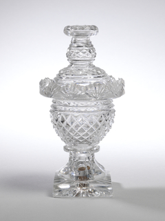Urn shape on square star out base. Flat fluted skin and foot with rug knop. All over diamond cut pattern with prismatic rings. Upturned rim with fan flutes and baluster finial with pierced, radial cut button top pierced with holes.