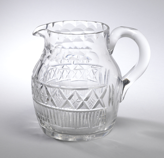 Circular body, flat base, tapered neck, small pouring spout, loop handle, sides faceted at bottom edge, above that a row of this vertical fluting, a row of diamonds filled alternately with 6-pointed stars or small diamonds, a row of wide facets, around the neck hollow faceting, the top rim fluted.