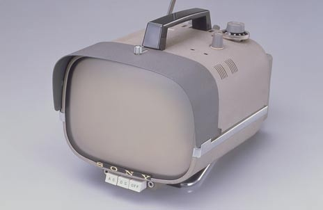 Portable television with square screen set in long rectangular gray metal housing with rounded edges; moveable visor at front; black plastic handle at top, retractable antenna at top left rear, station dial and volume control dial at top right rear; three square white control buttons on bottom front under the name SONY; metal base.