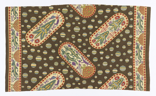 Length of printed cotton with shield-shaped medallions with borders of red diamonds or ovals. Each sheild is decorated with a mask or crocodiles. Placed at opposing angles on a dark gray ground with dots of various sizes, filled with blue, green, yellow, pink and white zig-zags.  Borders on two sizes with crocodiles and sea creatures.