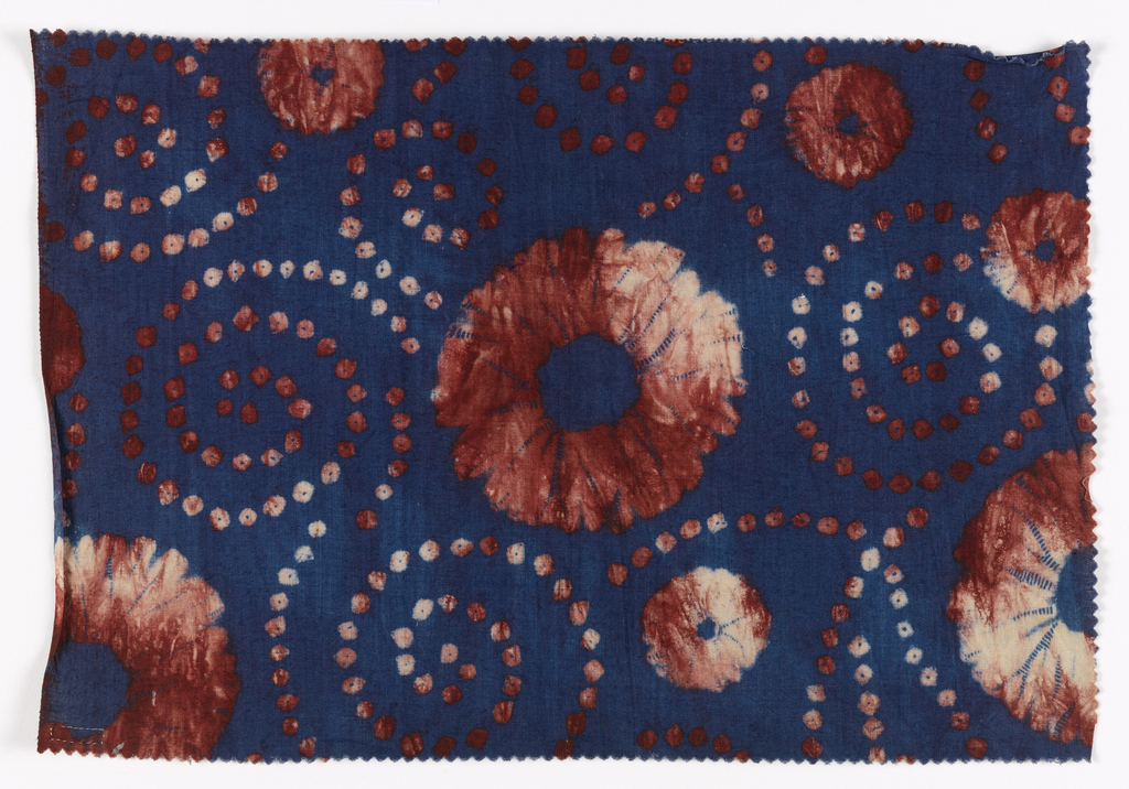 Cotton printed in imitation of tie-dye. Large and smaller rosettes and spirals of small dots, in mottled brick red on a deep blue ground.