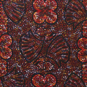 Length of cotton printed in crudely-executed imitation batik. Design of wings and stylized floral forms with a dense pattern of small circles filling the ground. In dark blue, yellow and red with crackle effect.