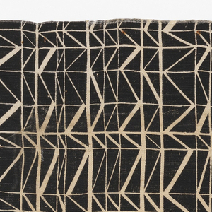 Printed textile with a grid of fine white lines and zig-zag lines giving a three-dimensional effect, on a printed black background.