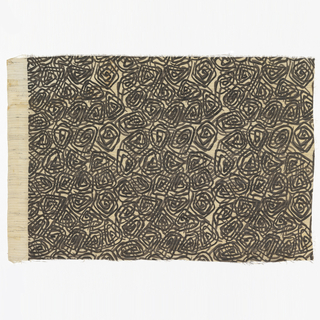 Length of printed fabric with a pattern of closely-spaced black and dark grey spirals on white ground.