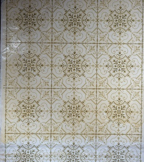 Full width. Sanitary paper composed of simulated tiles, with green lines marking the squares and three units of design to the width of the paper. Simple radial geometric figure set with foliage scrolls. Printed in yellow-green on plain ground.