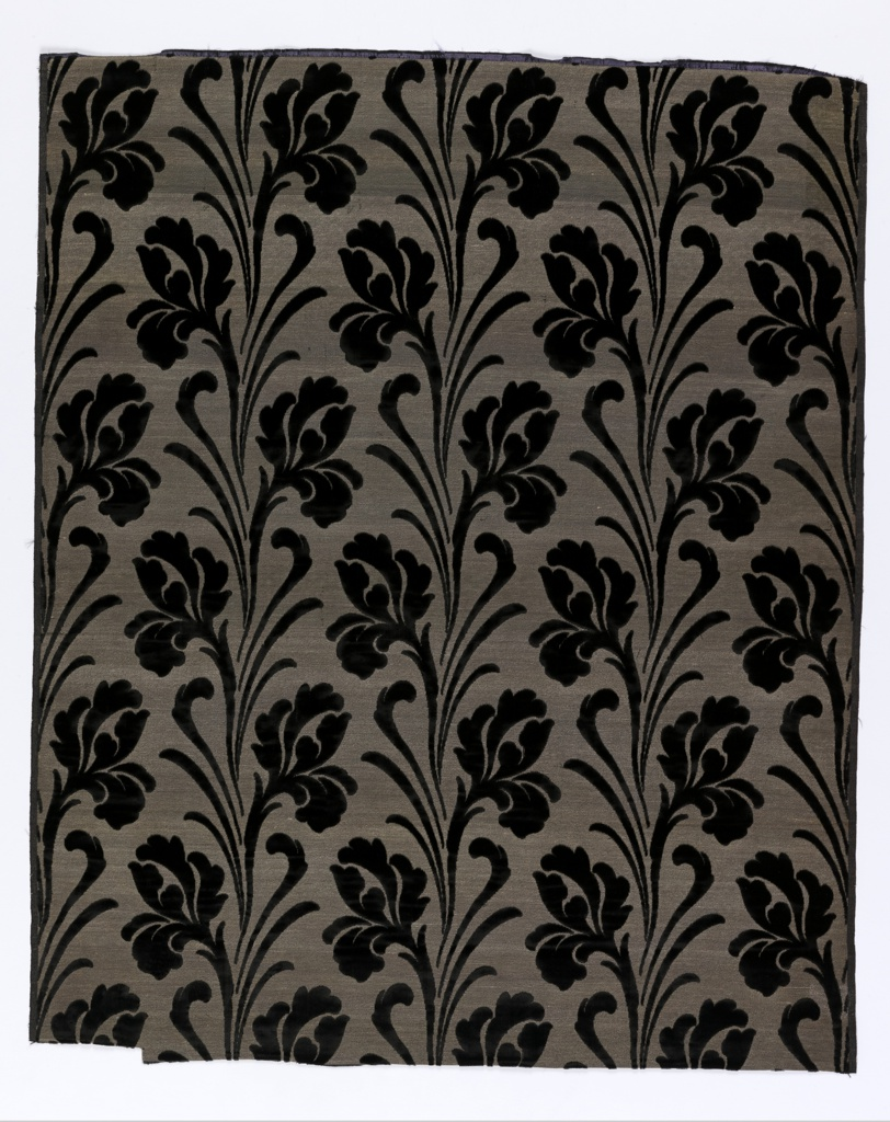 Ground shot with frisé silver or gold thread. Large-scale vertical repeat of conventionalized iris in black cut velvet. Ground color given by main silk warp. Black.