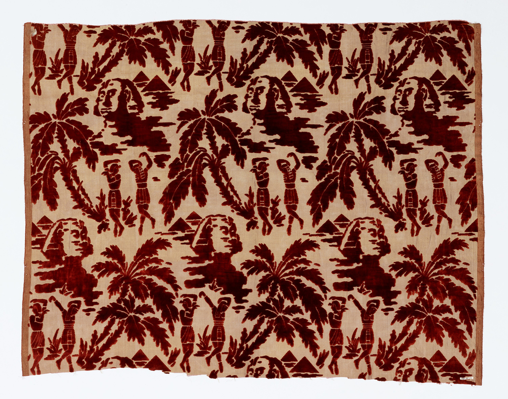 Sheer gold ground fabric with red pile in a design of two Egyptian figures dancing in a setting of palm trees alternating with sphinxes and pyramids.