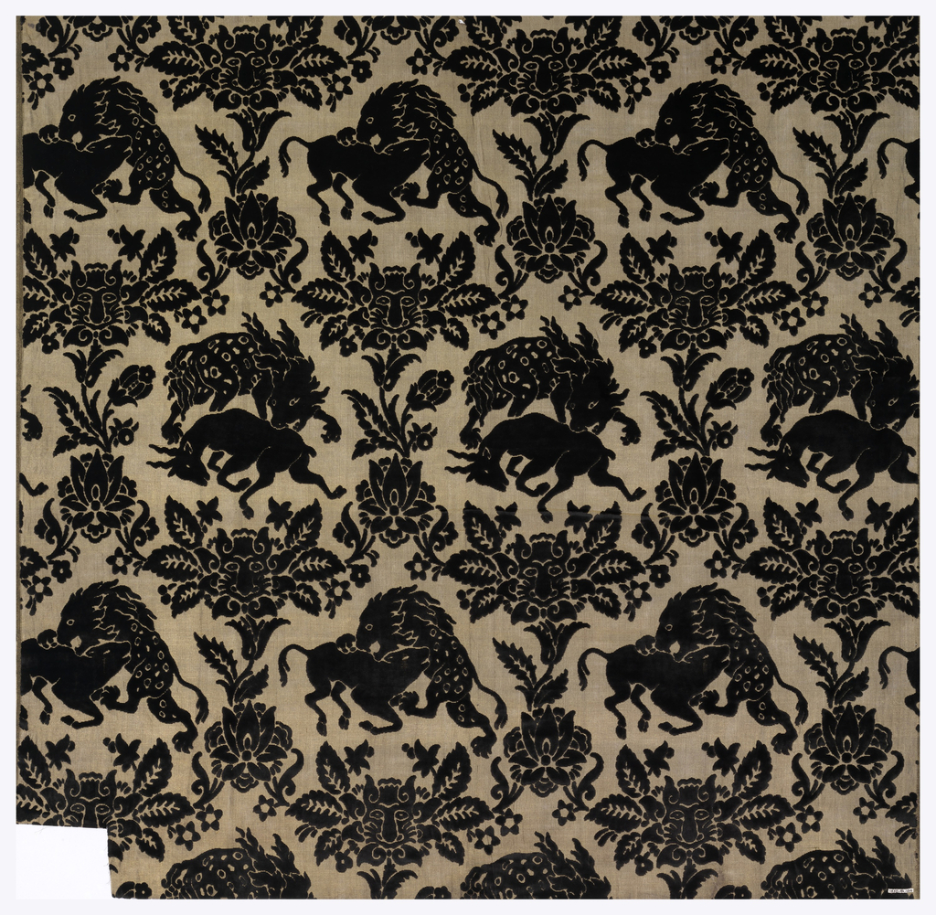 Sheer gold ground fabric with black pile in a design of a lion attacking a stag alternating with a lion attacking a calf. Surrounding the animals are festoons of flowers. Some flowers have tiger masks.