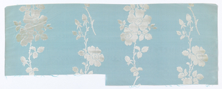 Vertical bands of wild roses in white velvet on a ribbed pale blue ground.
