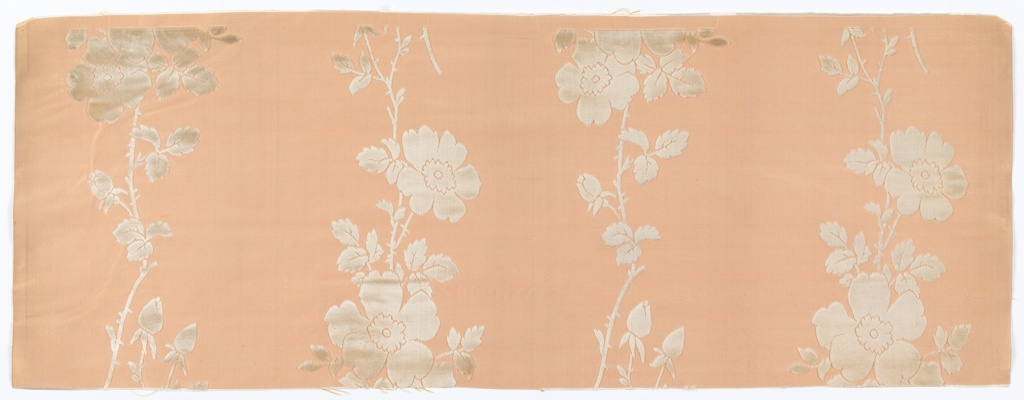 Vertical bands of wild roses in white velvet on a ribbed pale orange ground.