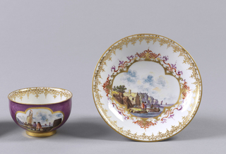 "Cup hemispherical, with slight outcurving at edge; cylindrical foot; no handle. Saucer shallow, curved side, slight outcurving at edge. Outside of cup and saucer decorated with slightly mottled red-violet, in which on cup are two four-lobed reserve panels enclosing seaport scenes. Upper face of saucer decorated with seaport enclosed in framework of gilding and colored scrolls. Gilt ""lace"" borders."