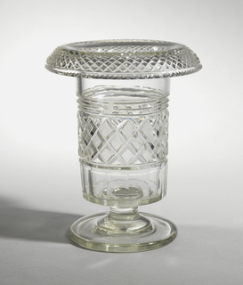 Tall straight-sided bow with wide turned-over rim and flat bottom spool stem on wide flat circular base; turned-over rim cut with all-over diamond pattern, notched at rim, band of strawberry diamonds center of side, prismatic band above, fluting below; glass slightly greenish.