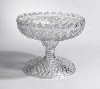 Large shallow circular bowl with scalloped edge, rim cut with fans, sides with undulating strawberry diamond pattern; base has waisted stem cut with prismatic rings; a band of strawberry diamonds above and a wide domed spreading foot with strawberry diamonds.