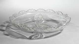 Shallow oval bowl with shaped rim; fan cutting on rim, central oval medallion with four smaller ones surrounding, all cut with stars; 4 swags cut with vertical flutes hang below lip.