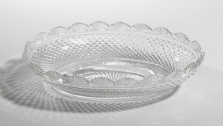 Shallow oval bowl with flat, oval base, radial cut. Body cut with sharp diamonds of graduated size. Fan scalloped rim with saw tooth top.