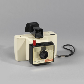 """Rectangular off-white plastic body with black lanyard strap on right, black eyepiece with viewer on top; front with projecting lens within black rectangular frame having red and white shutter button on tope and textured metalic front with text at bottom: """"POLAROID / LAND CAMERA"""" and """"SWINGER / Model 20""""."""