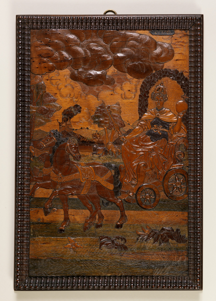 """Panel in gadrooned frame. Female figure, crowned, holding sceptre and orb, seated under laurel wreath in chariot, drawn by a pair of horses; in background, grazing cattle and a burning castle. At top right, labeled """"Europa""""."""