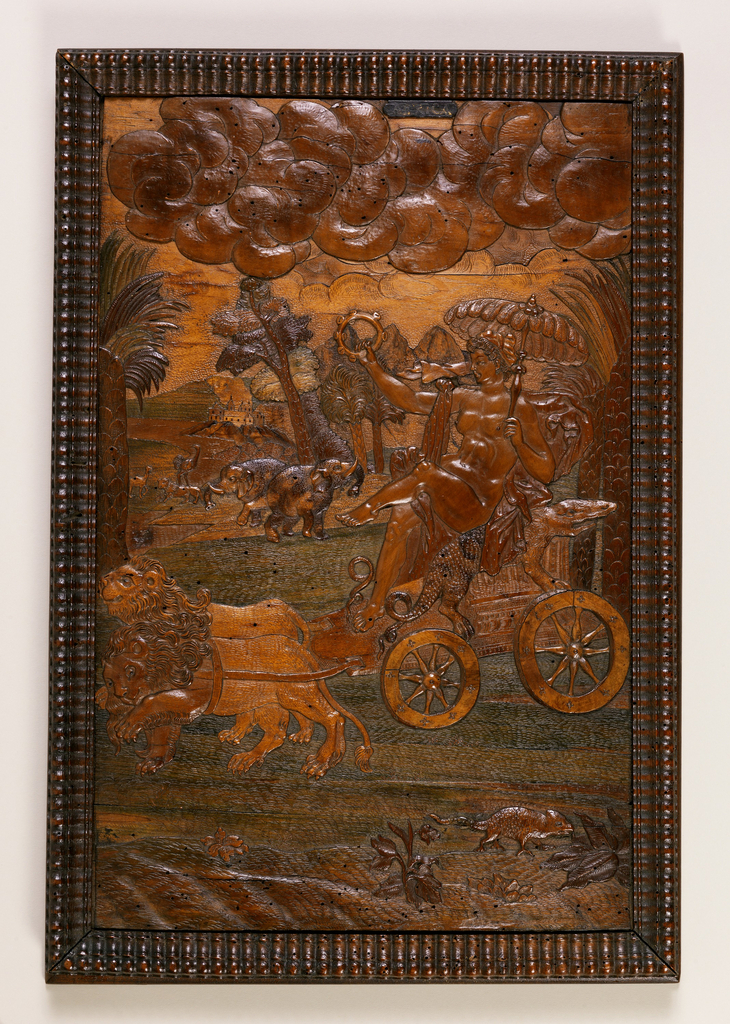"Panel in gadrooned frame. Nude female figure, holding tambourine and feather parasol, seated in chariot with crocodile arm rests, drawn by two lions; in foreground, scaly quadruped; in background, two elephants, camel, lion and ostrich. At top right, labeled ""Africa""."