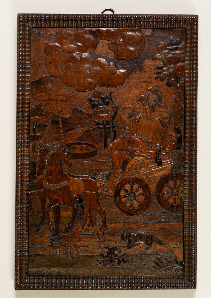 """Panel in gadrooned frame. Semi-nude female figure with feather headdress, holding bow and sceptre, seated in chariot drawn by two unicorns; in foreground, an armadillo in background, men with bows inside and outside a circular enclosure.  At top right, the word """"America"""" is faintly visible."""