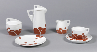 Tall slightly conical form with broad, flat triangular handle with circular opening; small curved triangular spout; white ground overall, the bottom decorated with various sized circles, some overlapping; white lid with large flat triangular handle with pierced circle at back. Part of a set that includes a covered sugar bowl, milk jug, cup and saucer, and plate.