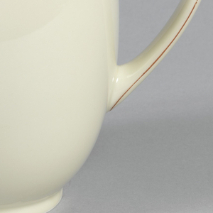Molded creamy-grey porcelain body. (a) Ovoid body with circular foot ring and flared circular neck. Loop handle opposite tapered curved spout. Red line around neck, around juncture of spout and body, and in middle of handle on both sides. (b) Cover with internal bezel; exterior flat and centered with outward-tapered flat-topped finial. Red line around edge of cover and around top and bottom of finial.