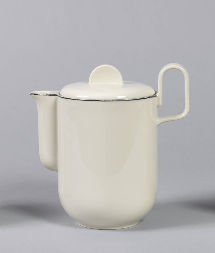 """Creamy-grey porcelain body. Coffee pot (a)  is cylindrical in shape, with curved lower section that tapers to circular foot. Spout is upright, with curved and cylindrical, attached along the entire length of the spout. Handle is placed high on body, formed like upright reversed """"U."""" Cover (b) is slightly domed, fitted with flange for closure, with flat semi-circular upright finial. Platinum band painted around lip and spout."""