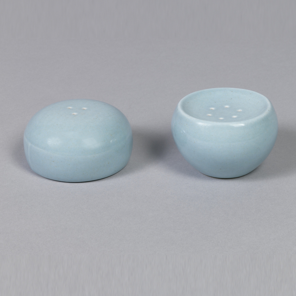 """Circular shaker (a)  tapering to base, slightly depressed circular top pierced with six holes; cork stopper (b) in bottom; """"ice blue"""" glaze."""