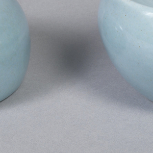 "Shaker (a) of squat globular form pierced with three holes at top, cork stopper (b) in bottom; ""ice blue"" glaze."