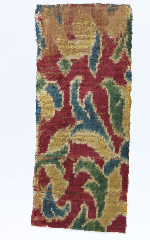 Double velvet weave with dark red on one side and a foliate pattern in blue, yellow, green and white ikat on a red ground.