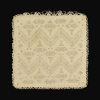 Pillow cover ornamented in conventional design worked in cutwork and embroidery. Joined to the back with bobbin lace. Pillow covered in green silk.