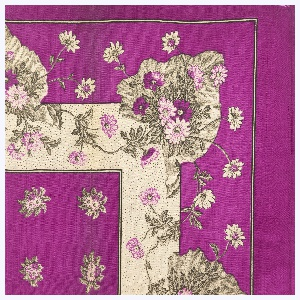 Quarter of a printed scarf in magenta, pink, cream-color, and black. Field of scattered flowers and border showing bunch of flowers on large leaf.