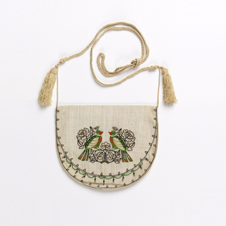 U-shaped white purse with a fold-over flap, with a pair of exotic birds and stylized flowers in black, green and orange; with a fine scalloped line of black embroidery around the edge and accented with beads. Long white cord with two tassels.